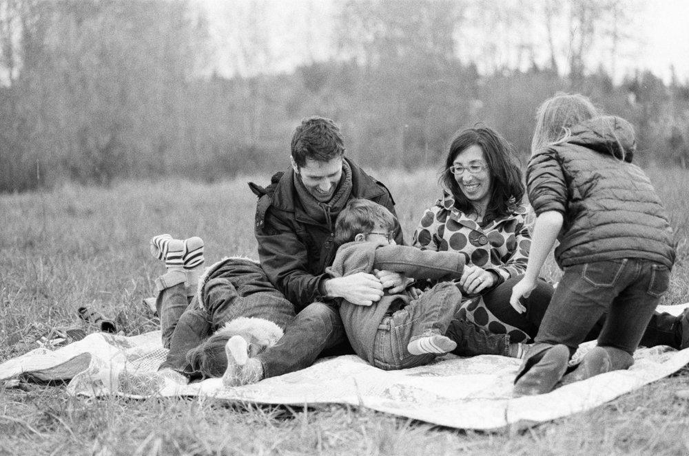 Bryant family photographer : dad tickling kids sitting on a blanket in a field