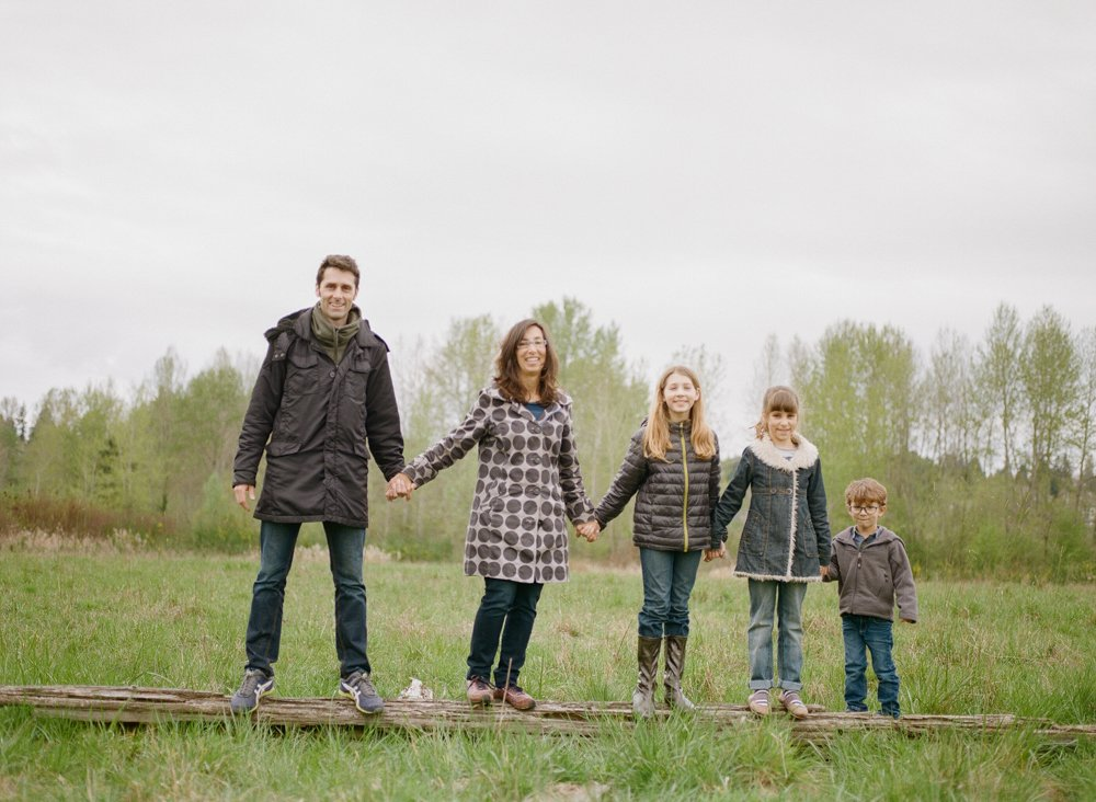 Bryant family photographer : family standing on a log together looking at camera
