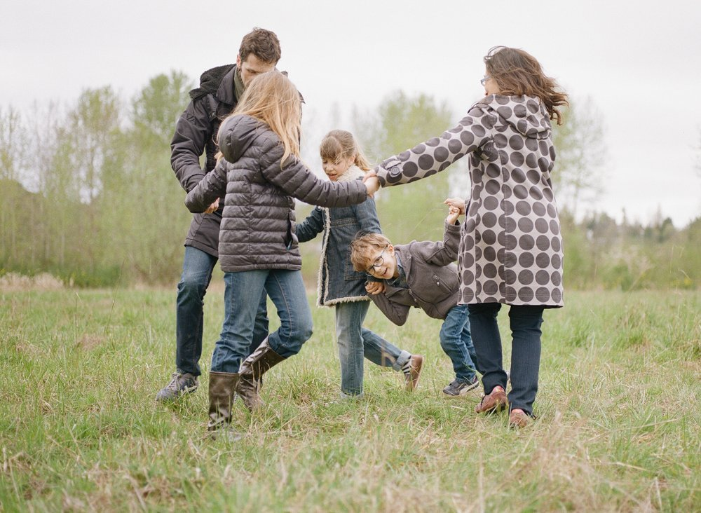 Bryant family photographer : family playing ring around the rosy in a field