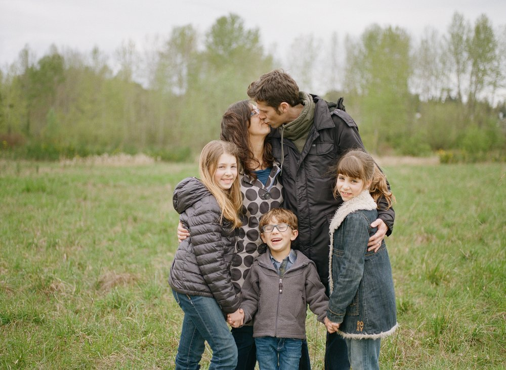 Bryant family photographer : parents kissing while kids are laughing