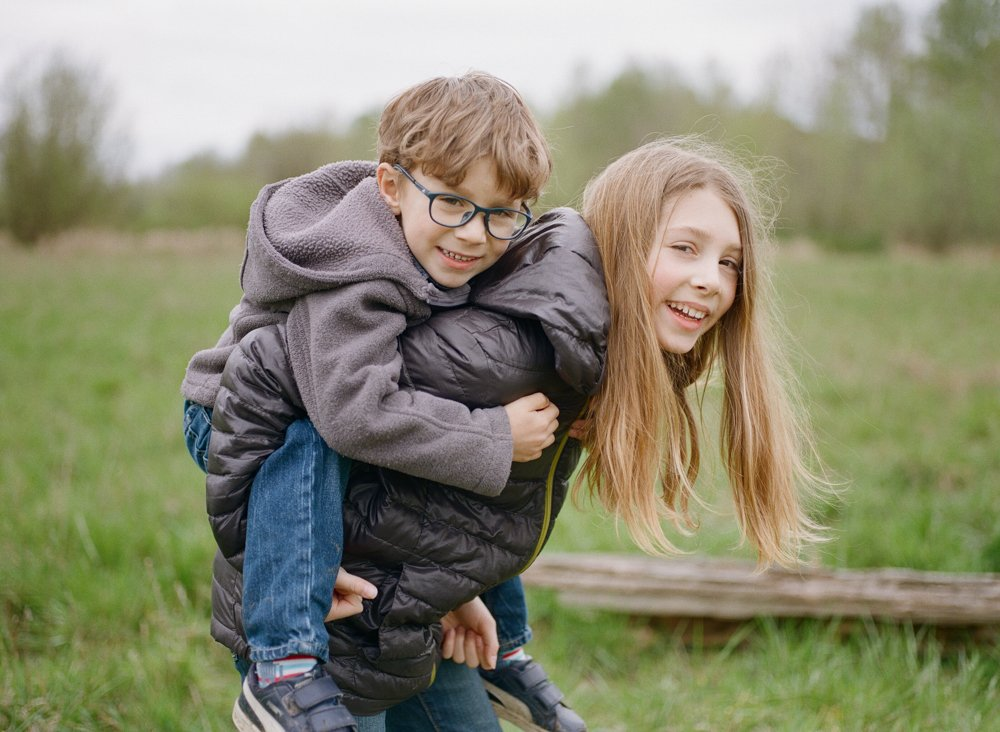 Bryant family photographer : older sister doing piggyback with younger brother