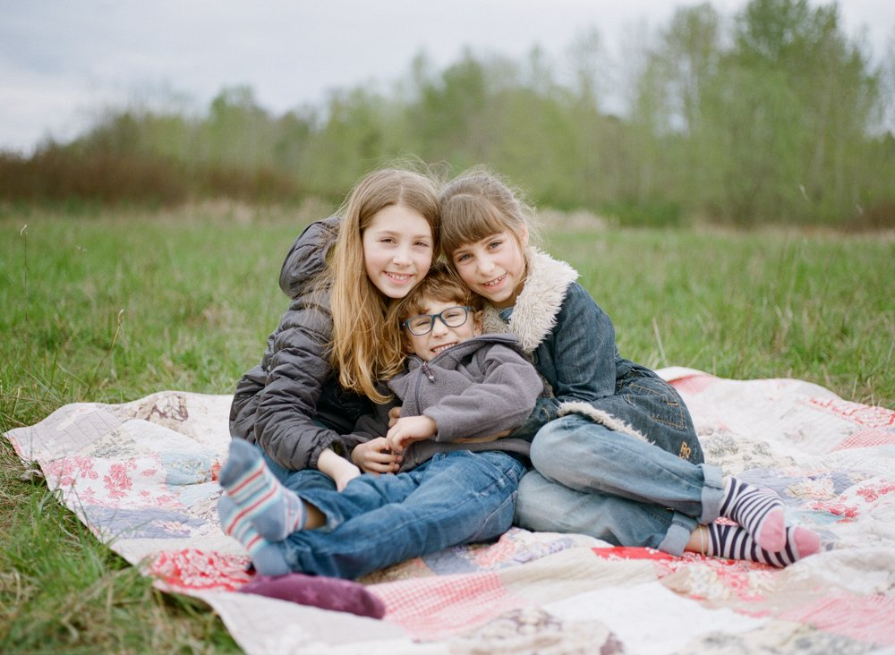 Bryant family photographer : three siblings cuddling on blanket in a field