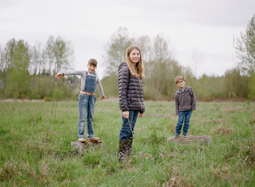 Bryant family photographer : three siblings standing on stumps in a seattle field