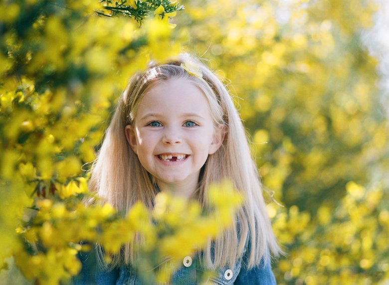 Seattle family photo session : daughter smiling surrounded by yellow flowers looking straight at camera