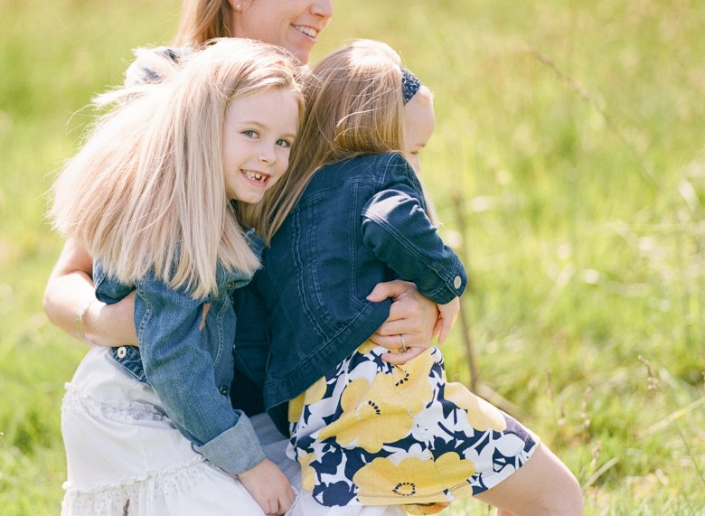 Seattle family photo session : mom holding daughters and smiling in field