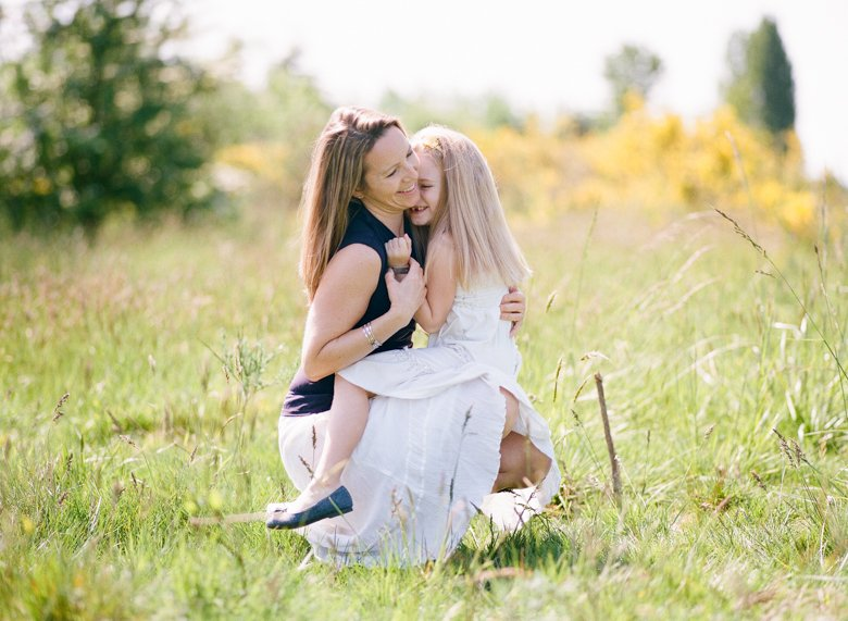 Seattle family photo session : mom and daughter laughing and cuddling in field