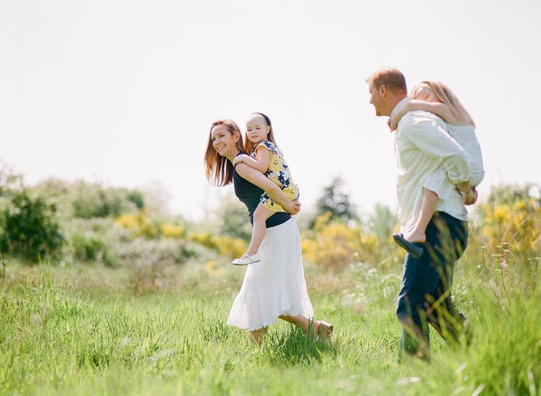 Seattle family photo session : kids riding piggyback on mom and dad in field