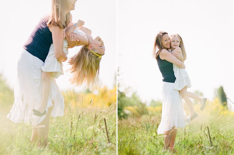 Seattle family photo session : mom standing holding up daughter and hugging her