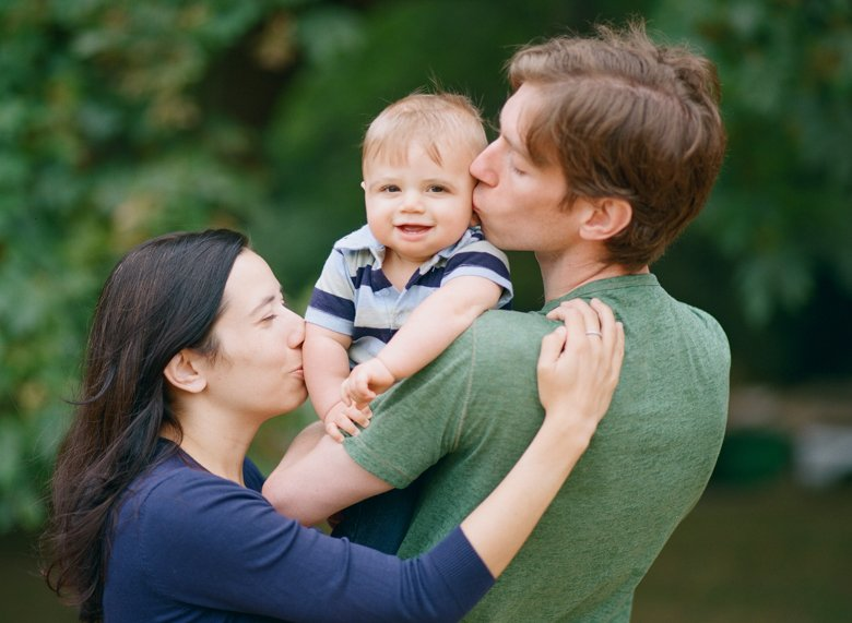 Seattle baby photography : mom and dad kissing 6 month old baby outside