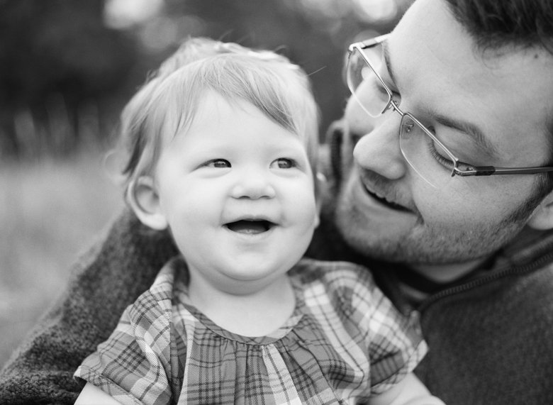 family photographer northeast Seattle : dad looking down smiling at little girl