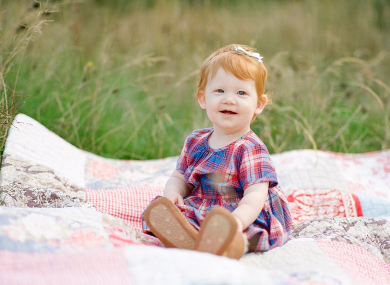 family photographer northeast Seattle : toddler sitting on blanket smiling at camera
