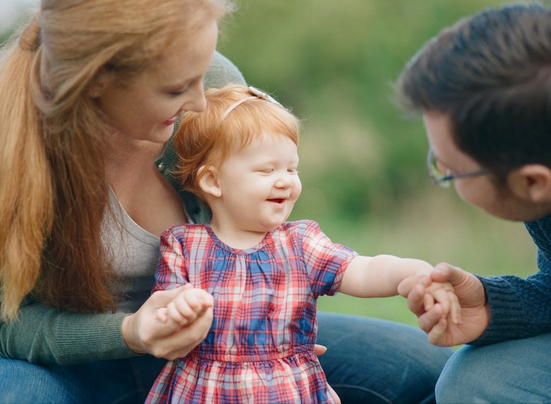family photographer northeast Seattle : parents holding toddler girl's hand