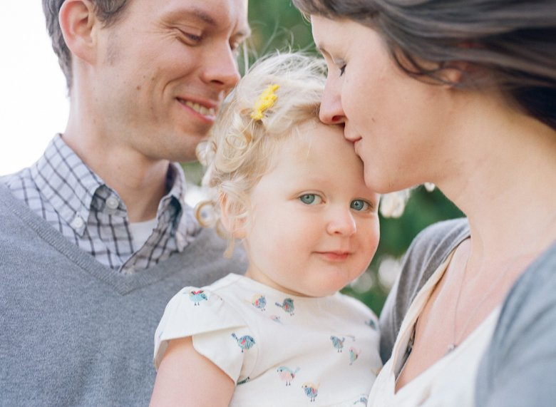 Seattle extended family photographer : grand daughter smiling at camera while mom kisses her
