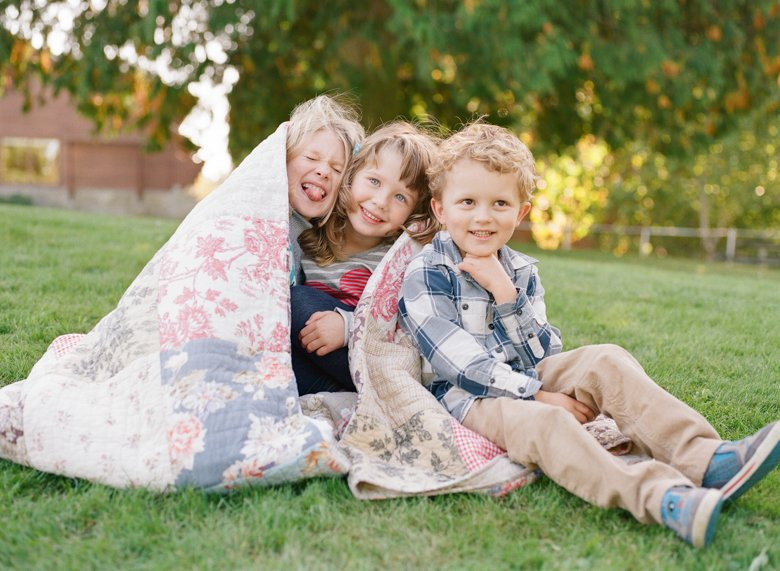 Seattle extended family photographer : three cousins having fun under a blanket