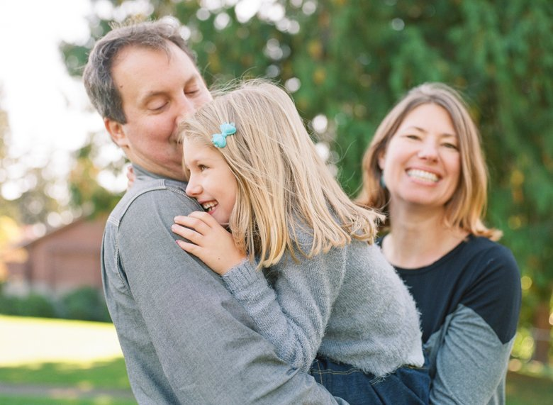 Seattle extended family photographer : candid father mother daughter picture with both laughing