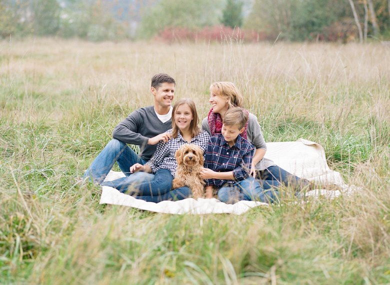 family photography with dogs Seattle : family of four sitting in field with dog