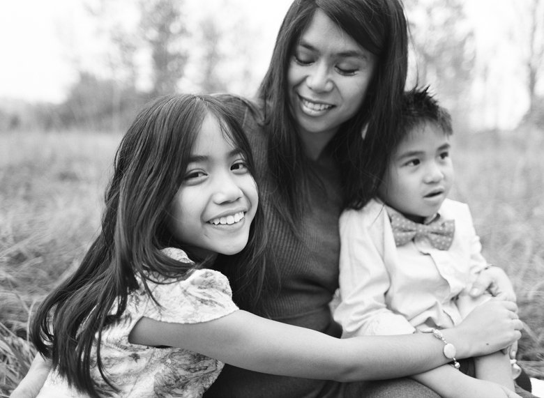 outdoor family photographs Seattle : tween girl looking and smiling at camera hugging mom and brother