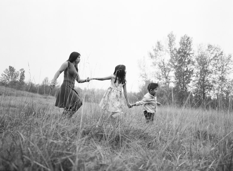 outdoor family photographs Seattle : mom and kids walking in field holding hands