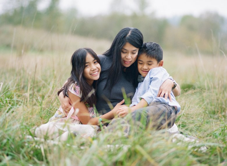 outdoor family photographs Seattle : mom cuddling two kids in grassy field
