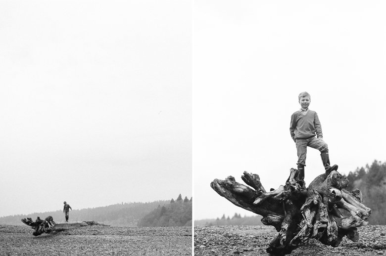 family photographer north seattle : black and white photo of boy standing on big log at the beach