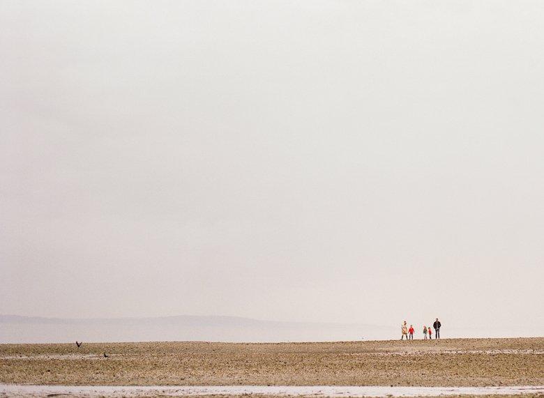 family photographer north seattle : family on rocky beach far away