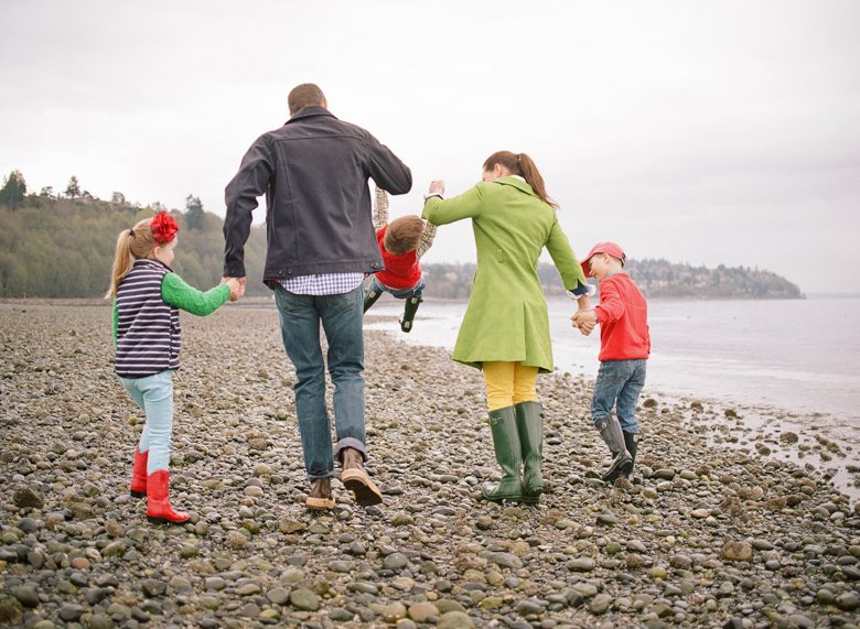family photographer north seattle : family holding hands swinging youngest child into air