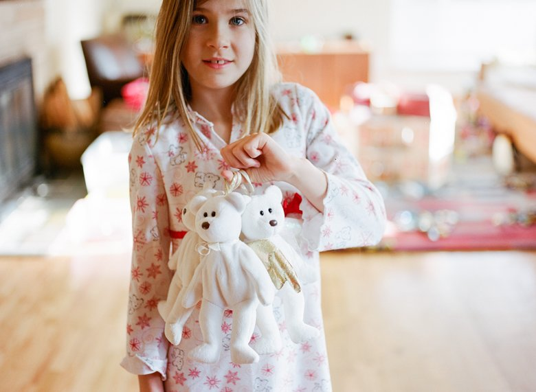 why film : girl in pajamas holding white beanie baby bears