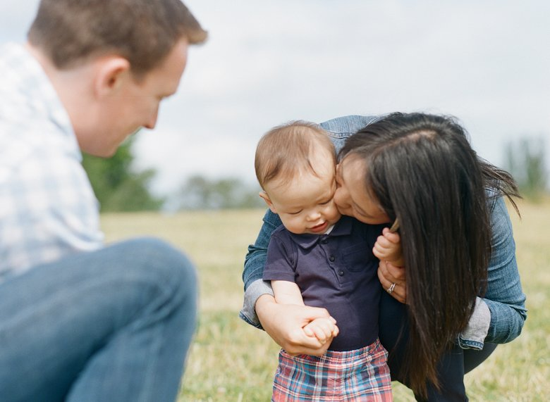 outdoor seattle family photo session magnuson park : mom kissing baby