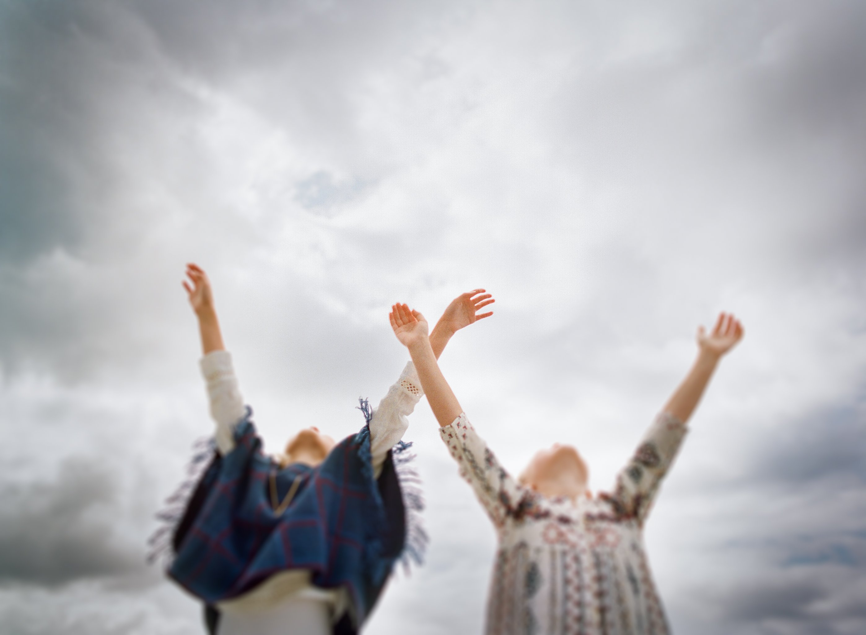 best family photographer seattle | sisters with arms raised towards sky