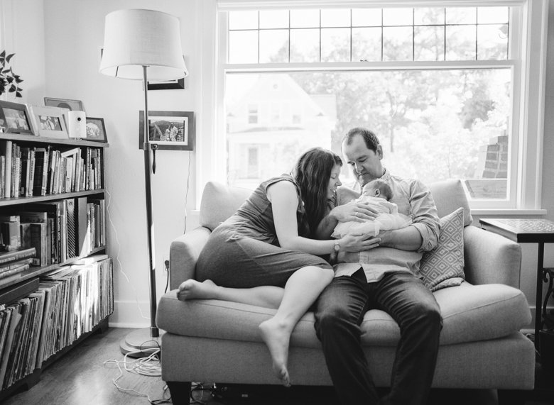 north seattle newborn photography in home session : family fawning over newborn while sitting on living room couch