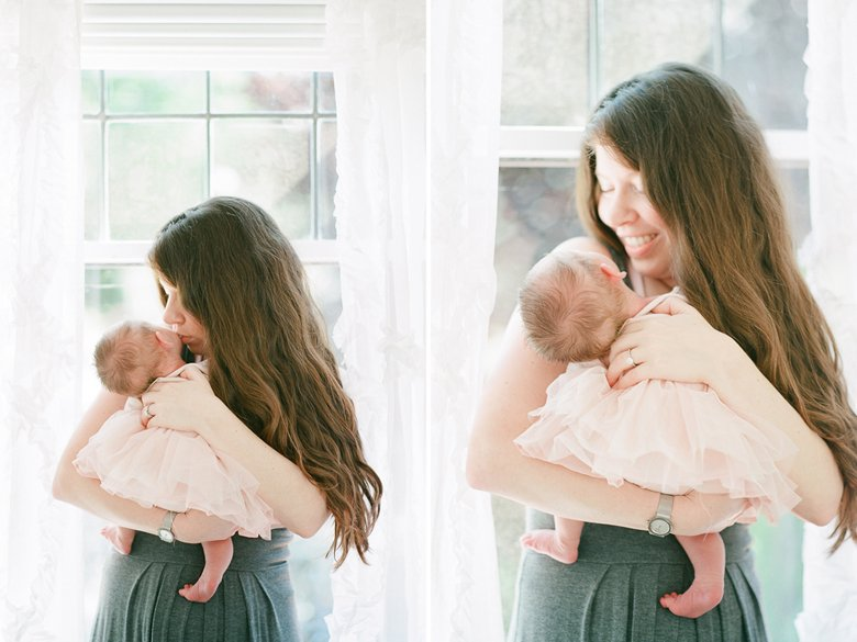 north seattle newborn photography in home session : mom cuddling newborn by window