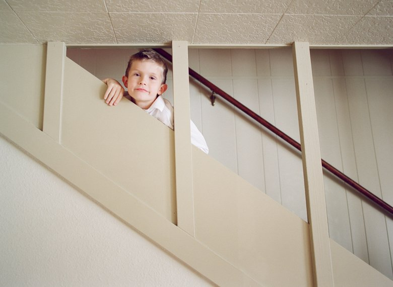 in home candid family photo session | boy on stairs