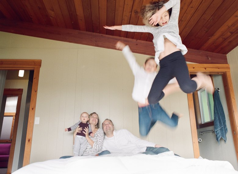 in home candid family photo session | kids jumping on bed