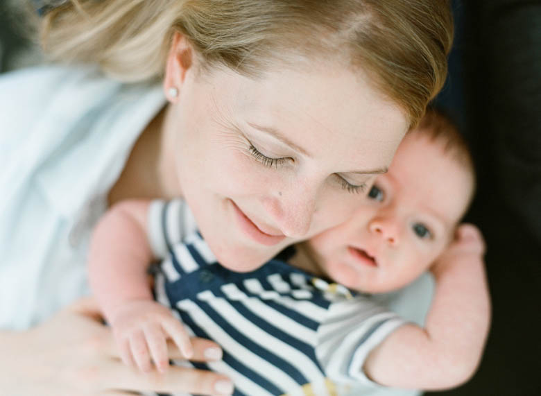 in-home family photos Seattle WA : mom cuddling baby smiling