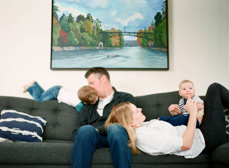 in-home family photos Seattle WA : family hanging out on couch in living room with young boys