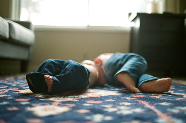 in-home family photos Seattle WA : young boys laying on rug with focus on bare feet