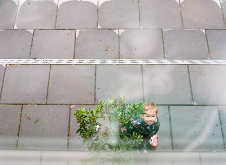 in-home family photos Seattle WA : boy looking up at camera from patio