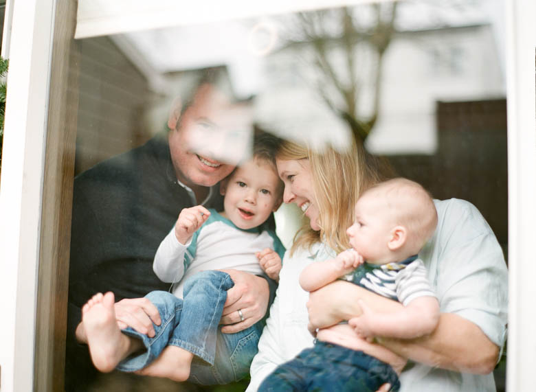 in-home family photos Seattle WA : family cuddling and smiling by window