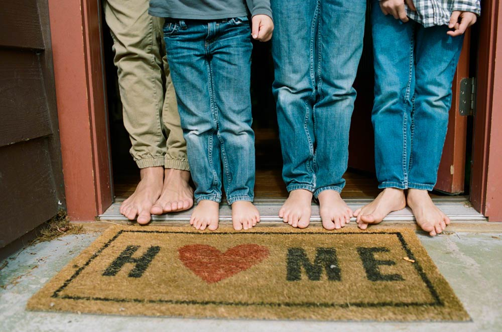 Seattle in home family photography : four sets of kids feet standing on welcome mat