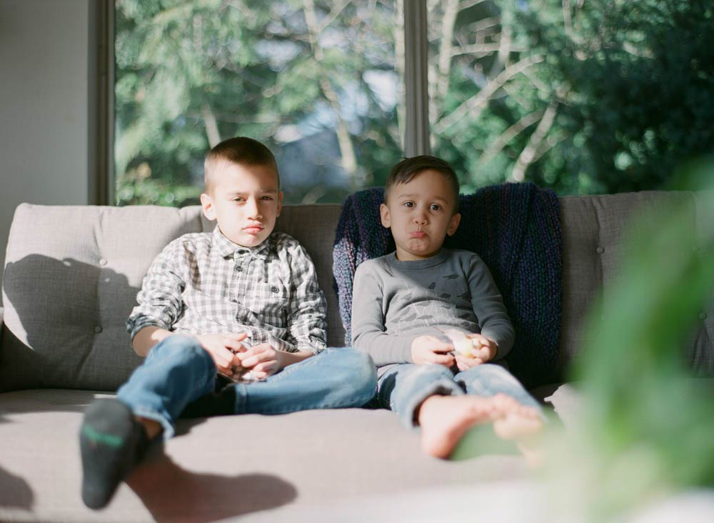Seattle in home family photography : brothers sitting on couch looking at camera