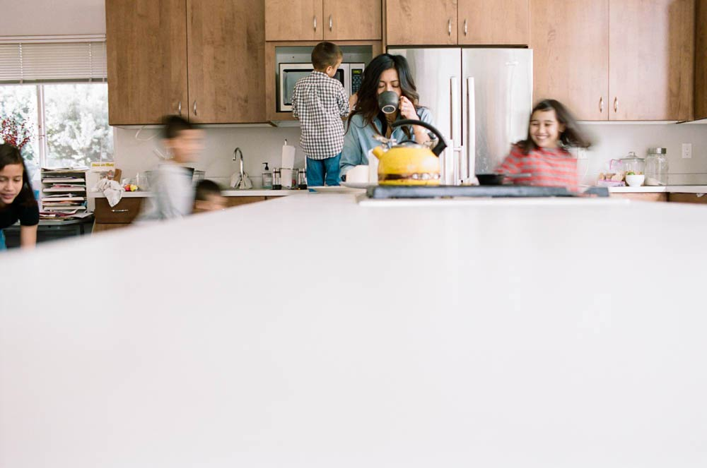 Seattle in home family photography : mom drinking coffee while kids blurred behind her