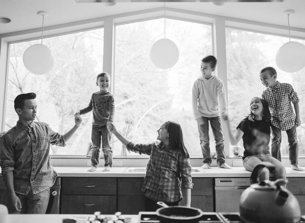 Seattle in home family photography : six siblings standing on kitchen counter holding hands