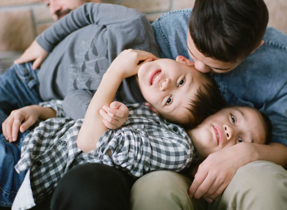 Seattle in home family photography : older brother kissing middle brother's forehead