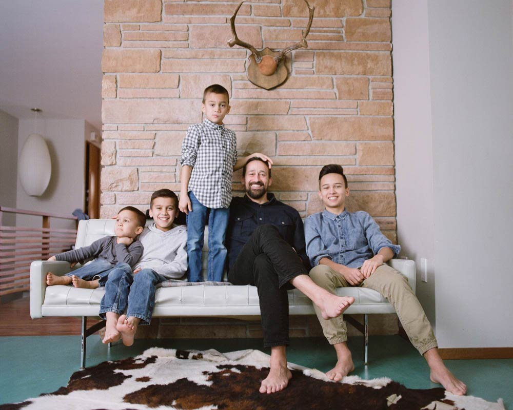 Seattle in home family photography : dad and four sons sitting on couch looking at camera