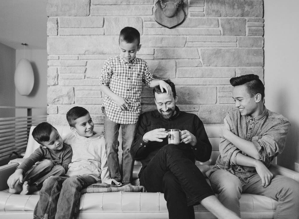 Seattle in home family photography : dad drinking coffee and laughing with four sons