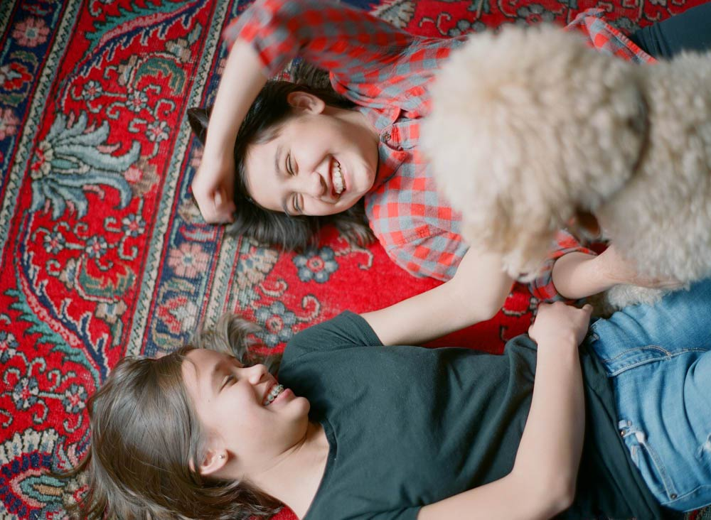 Seattle in home family photography : sisters laying on red rug laughing with dog