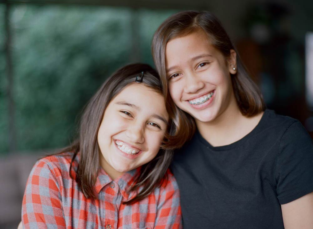 Seattle in home family photography : sisters smiling and looking at camera