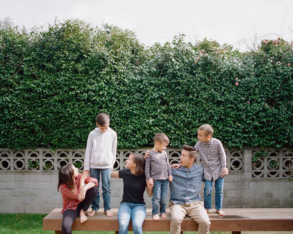 Seattle in home family photography : six siblings outside on deck standing on bench