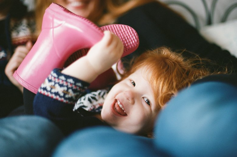 child photography Seattle : girl holding pink rain boot smiling at camera