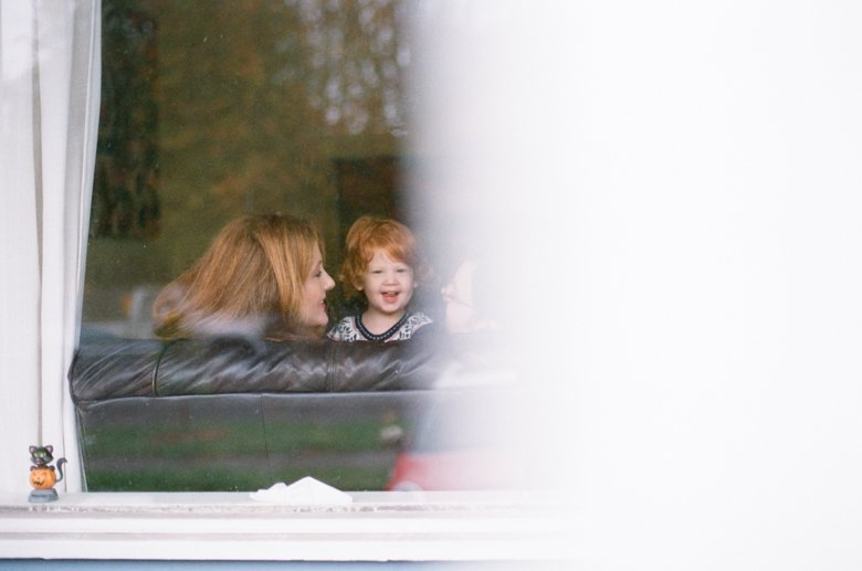 child photography Seattle : family cuddling on couch through window